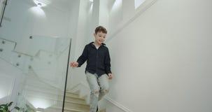 Menino feliz na manhã que corre para baixo ao primeiro andar pronto para a escola, tem um grande humor