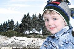 Menino feliz na roupa do inverno no parque do lago na neve Fotos de Stock