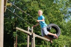 Menino feliz no campo de jogos no parque fotografia de stock