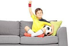 Menino feliz no sportswear com um futebol que senta-se em um sofá e em um ge imagens de stock royalty free