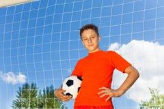 Menino feliz no t-shirt alaranjado com futebol Fotografia de Stock
