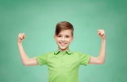 Menino feliz no t-shirt do polo que mostra os punhos fortes imagem de stock royalty free