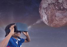 Menino feliz nos auriculares de VR que olham acima a um planeta 3D contra o fundo roxo com alargamento Fotografia de Stock Royalty Free