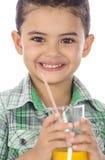 Menino feliz pequeno que bebe um vidro do suco fotografia de stock