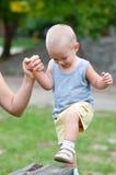 Menino feliz pequeno que escala a coluna de madeira no campo de jogos exterior Fotos de Stock Royalty Free