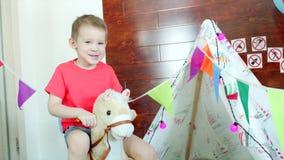 Menino feliz pequeno que monta um cavalo do brinquedo na sala de jogos filme