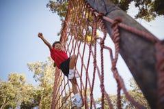 Menino feliz que cheering ao escalar uma rede durante o curso de obstáculo fotos de stock