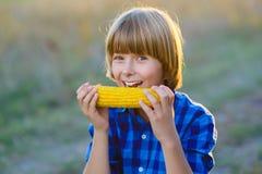 Menino feliz que come a espiga de milho saudável fotografia de stock royalty free