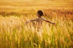 Menino feliz que corre na grama em uma noite do verão Imagens de Stock