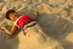 Menino feliz que encontra-se para baixo na praia Foto de Stock