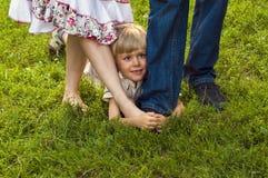 Menino feliz que esconde nos pés dos pais imagens de stock