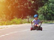 Menino feliz que está no hoverboard ou no gyroscooter com acesso do kart imagens de stock