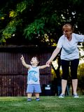 Menino feliz que faz as caras engraçadas e as expressões ao andar com sua avó fotos de stock