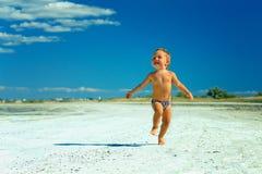 Menino feliz que funciona a estrada perto do beira-mar Fotos de Stock