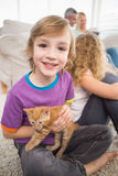 Menino feliz que guarda o gatinho ao sentar-se com família imagens de stock