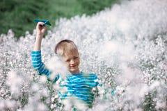 Menino feliz que inclina e que joga o avião de papel azul na SU brilhante imagens de stock royalty free