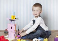 Menino feliz que joga com brinquedos Fotografia de Stock Royalty Free