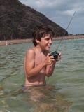 Menino feliz que joga com o brinquedo remoto no oceano Imagem de Stock