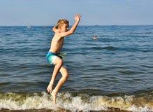 Menino feliz que joga na praia foto de stock royalty free