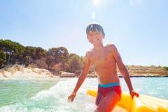 Menino feliz que joga nas ondas com flutuador inflável imagens de stock royalty free
