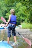 Menino feliz que kayaking no rio fotografia de stock