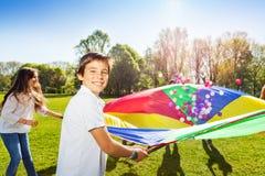 Menino feliz que mantém o paraquedas completo de bolas coloridas Fotografia de Stock
