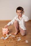 Menino feliz que recolhe o dinheiro em seu mealheiro e que fala o telefone Fotografia de Stock Royalty Free