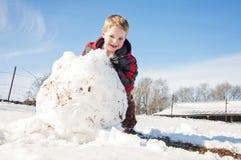Menino feliz que rola a bola de neve enorme Foto de Stock Royalty Free