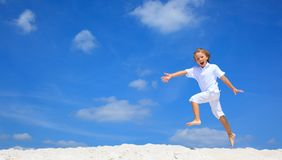 Menino feliz que salta na praia Imagens de Stock