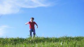 Menino feliz que salta no monte da grama verde video estoque