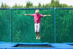 Menino feliz que salta no trampolim imagens de stock royalty free