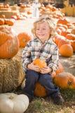 Menino feliz que senta e que guarda sua abóbora no remendo da abóbora Imagens de Stock Royalty Free