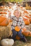 Menino feliz que senta e que guarda sua abóbora no remendo da abóbora Imagem de Stock