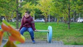 Menino feliz que senta-se em um banco no parque e que ri no parque Mo lento filme