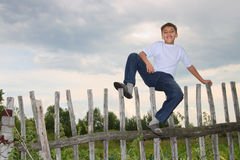 Menino feliz que senta-se na cerca Imagens de Stock Royalty Free