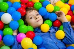 Menino feliz que tem o divertimento no poço da bola na festa de anos no parque de diversões das crianças e no centro interno do j fotografia de stock