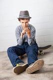 Menino fresco que senta-se em seu skate, guardando um smartphone Foto de Stock