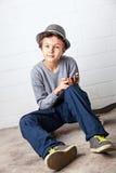 Menino fresco que senta-se em seu skate, guardando um smartphone Imagens de Stock