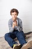 Menino fresco que senta-se em seu skate, guardando um smartphone Imagem de Stock Royalty Free