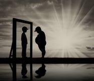 Menino gordo e sua reflexão no espelho de um menino normal contra o céu imagens de stock