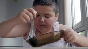 Menino gordo pequeno do retrato que senta-se na cozinha que come uma colher da sopa, obesidade da infância dos problemas filme