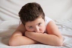 Menino gordo triste que encontra-se na cama Imagem de Stock