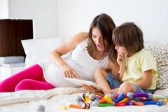 Menino grávido bonito da mãe e da criança que joga junto dentro Imagem de Stock