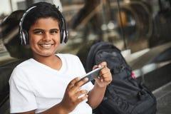 Menino hindu alegre que usa seus dispositivos espertos modernos imagens de stock