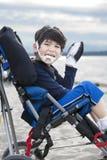 Menino idoso de cinco anos incapacitado feliz na cadeira de rodas Fotografia de Stock