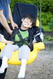 Menino idoso de cinco anos incapacitado no balanço da desvantagem Fotos de Stock Royalty Free