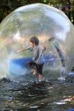 Menino idoso de cinco anos no short e na camisa cinzenta de t que equilibram dentro de uma bola enorme do zorb na água no parque  Foto de Stock