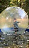 Menino idoso de cinco anos no short e na camisa cinzenta de t que equilibram dentro de uma bola enorme do zorb na água no parque  Imagens de Stock