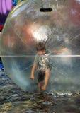 Menino idoso de cinco anos no short e na camisa cinzenta de t que equilibram dentro de uma bola enorme do zorb na água no parque  Fotos de Stock