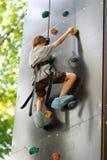 Menino idoso de cinco anos que aprende escalar a parede da rocha fora no parque do verão Fotografia de Stock